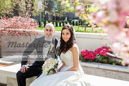 Portrait of Bride and groom sitting on stone bench in park in Spring, smiling and looking at camera, Canada Stock Photo - Rights-Managed, Image code: 700-07237621
