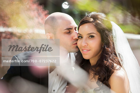 Close-up portrait of groom gving bride a kiss on cheek, sitting outdoors on Wedding Day, Canada Stock Photo - Rights-Managed, Image code: 700-07237622
