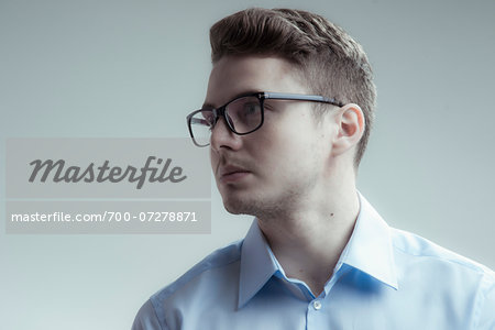 Close-up portrait of young man wearing eyeglasses and blue shirt, looking to the side, studio shot on white background