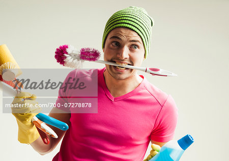 Close-up portrait of young man goofing around and holding colorful cleaning supplies, studio shot on white background Stock Photo - Rights-Managed, Image code: 700-07278878