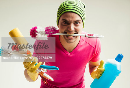 Close-up portrait of young man goofing around and holding colorful cleaning supplies, studio shot on white background Stock Photo - Rights-Managed, Image code: 700-07278879