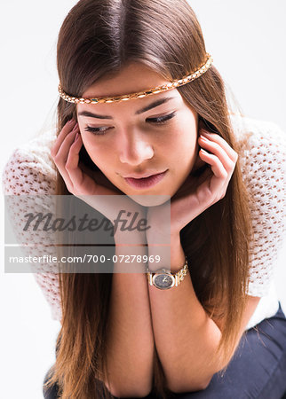 Portrait of young woman with long, brown hair, wearing headband, leaning on elbows and looking downwards, studio shot on white background Stock Photo - Rights-Managed, Image code: 700-07278969