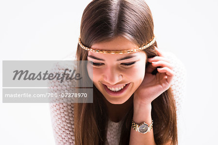 Portrait of young woman with long, brown hair, wearing headband, smiling and looking downwards, studio shot on white background Stock Photo - Rights-Managed, Image code: 700-07278970