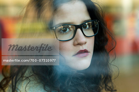 Close-up portrait of teenage girl wearing eyeglasses and looking out window, Germany Stock Photo - Rights-Managed, Image code: 700-07310977