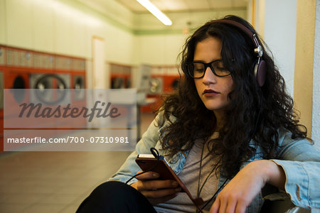 Teenage girl sitting in laundromat, wearing headphones and listening to music on smart phone, Germany Stock Photo - Rights-Managed, Image code: 700-07310981