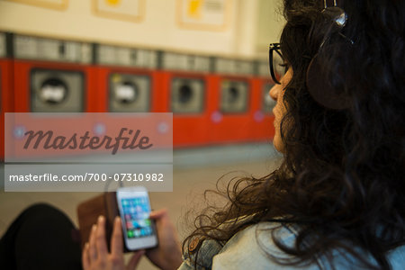 Teenage girl sitting in laundromat, wearing headphones and using smart phone, Germany Stock Photo - Rights-Managed, Image code: 700-07310982