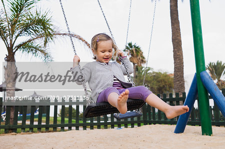 Three year old girl playing in playground on swing, Spain Stock Photo - Rights-Managed, Image code: 700-07311135