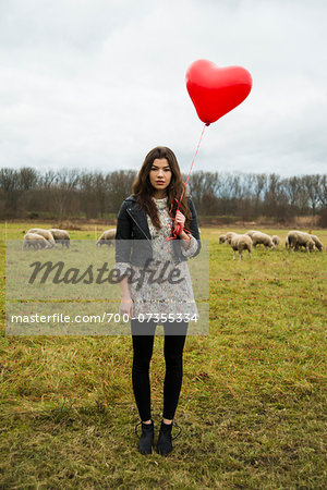 Young Woman with Heart-shaped Balloon by Sheep in Field, Mannheim, Baden-Wurttemberg, Germany Stock Photo - Rights-Managed, Image code: 700-07355334