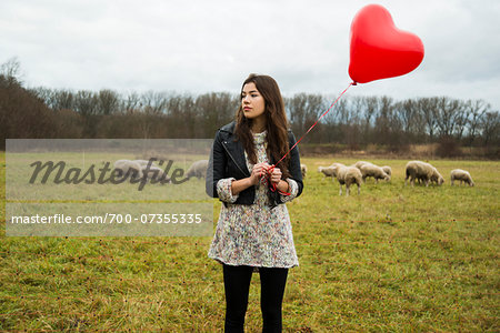Young Woman with Heart-shaped Balloon by Sheep in Field, Mannheim, Baden-Wurttemberg, Germany Stock Photo - Rights-Managed, Image code: 700-07355335