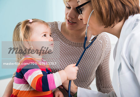 Doctor using Stethoscope on Baby Girl with Mother in Doctor's Office Stock Photo - Rights-Managed, Image code: 700-07453707