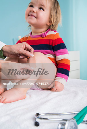 Doctor Putting Bandage on Baby Girl's Leg in Doctor's Office Stock Photo - Rights-Managed, Image code: 700-07453714