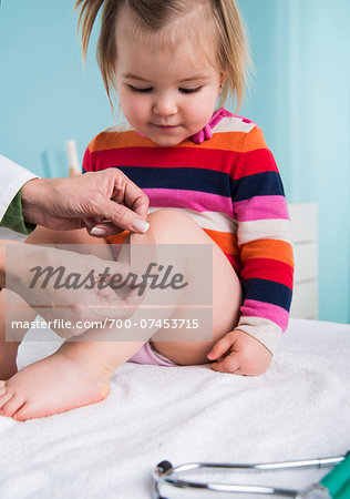 Doctor Putting Bandage on Baby Girl's Leg in Doctor's Office Stock Photo - Rights-Managed, Image code: 700-07453715