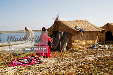 Woman in Peruvian clothing standing next to straw house, Floating Island of Uros, Lake Titicaca, Peru Stock Photo - Rights-Managed, Image code: 700-07529097
