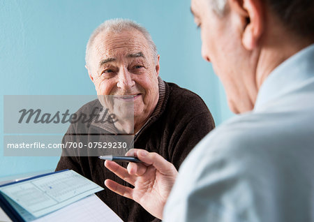 Senior male patient consulting doctor in office, Germany