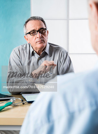 Senior, male doctor conferring with male patient in office, Germany Stock Photo - Rights-Managed, Image code: 700-07529240