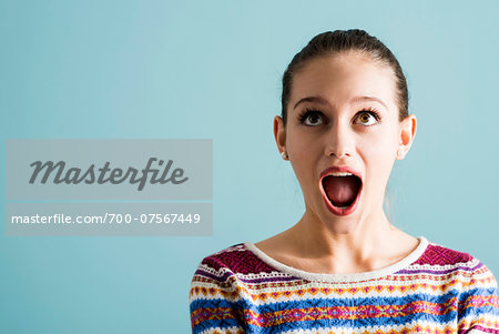 Close-up portrait of teenage girl, wide-eyed and with open mouth, studio shot on blue background Stock Photo - Rights-Managed, Image code: 700-07567449