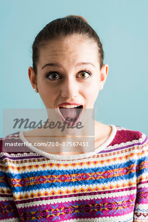 Close-up portrait of teenage girl, wide-eyed and with open mouth, studio shot on blue background Stock Photo - Rights-Managed, Image code: 700-07567451