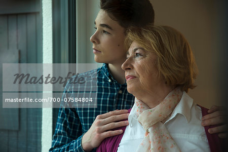 Close-up portrait of teenage boy with grandmother looking out window at home, Germany Stock Photo - Rights-Managed, Image code: 700-07584804