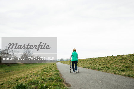 Backview of senior woman walking along path using walker in nature, Germany Stock Photo - Rights-Managed, Image code: 700-07584818