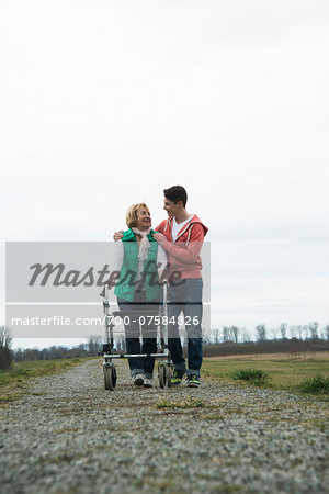 Teenage grandson with grandmother using walker on pathway in park, walking in nature, Germany Stock Photo - Rights-Managed, Image code: 700-07584826