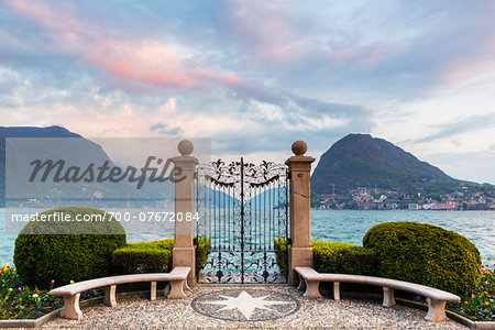 Ornamental topiary, globe shaped bushes next to wrought iron gate in Parco Civico in front of Monte San Salvatore in spring at sunset, Lugano, Switzerland Stock Photo - Rights-Managed, Image code: 700-07672084