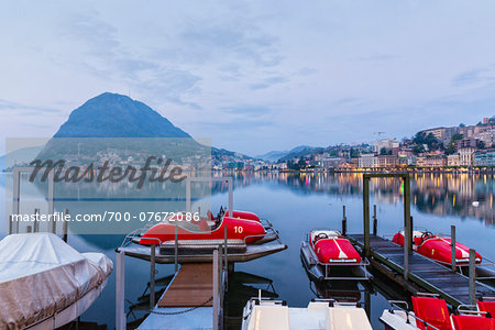 Moored pedal boats by the promenade in front of Monte San Salvatore and city lights at Lago Lugano at dawn in spring, Lugano, Switzerland Stock Photo - Rights-Managed, Image code: 700-07672086