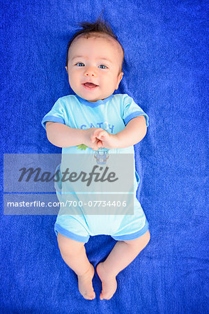 Portrait of three month old baby boy smiling and looking at camera, studio shot on blue background Stock Photo - Rights-Managed, Image code: 700-07734406