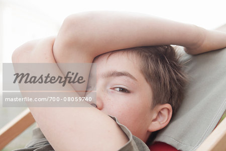 Close-up portrait of boy sitting in a deckchair looking at camera, with arm covering face, Vendome, Loir-et-Cher, France Stock Photo - Rights-Managed, Image code: 700-08059740