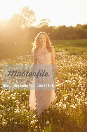 Young woman standing in a withered dandelion meadow in spring, Germany Stock Photo - Rights-Managed, Image code: 700-08080548