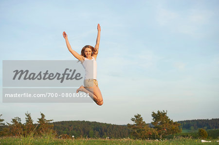 Young woman jumping in the air on a meadow in spring, Germany Stock Photo - Rights-Managed, Image code: 700-08080551