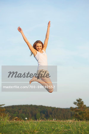 Young woman jumping in the air on a meadow in spring, Germany Stock Photo - Rights-Managed, Image code: 700-08080552