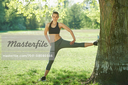 Close-up of a young woman exercising, stretching using a tree in a park in spring, Bavaria, Germany Stock Photo - Rights-Managed, Image code: 700-08080566