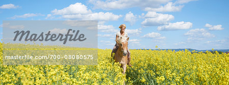 Young woman riding a Haflinger horse in a canola field in spring, Bavaria, Germany Stock Photo - Rights-Managed, Image code: 700-08080575