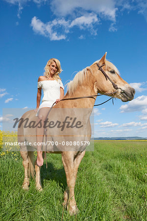 Portrait of young woman sitting on a Haflinger horse in a meadow in spring, Bavaria, Germany Stock Photo - Rights-Managed, Image code: 700-08080579