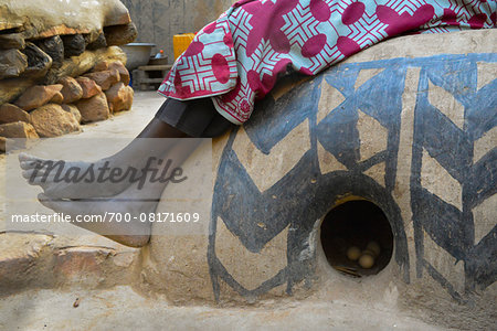 Close-up of woman's legs and feet, sitting on decorated round henhouse with eggs, Tiebele, Burkina Faso Stock Photo - Rights-Managed, Image code: 700-08171609