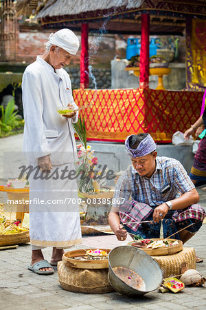 Hindu priest watches man light incense at a Bulan Pitung Dina (One Month and One Week) purification ceremony for baby and parents, Ubud, Bali, Indonesia Stock Photo - Rights-Managed, Image code: 700-08385867