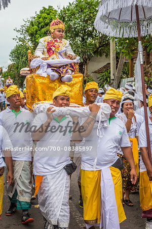 Boy being carried in a raised chair by people in a parade at a cremation ceremony for a high priest in Ubud, Bali, Indonesia Stock Photo - Rights-Managed, Image code: 700-08385897