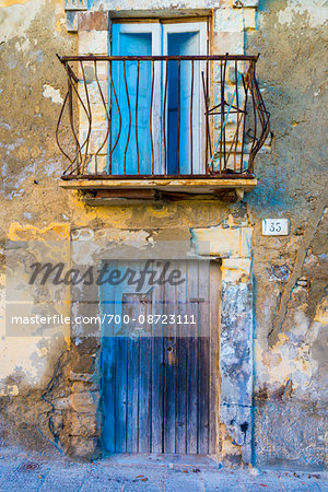 Worn, peeling stone walls on building with wooden doors and balcony in Ragusa in Sicily, Italy Stock Photo - Rights-Managed, Image code: 700-08723111