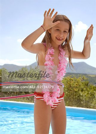 Young blonde girl with hula hoop and pink garland around neck by swimming pool Stock Photo - Rights-Managed, Image code: 822-02124379
