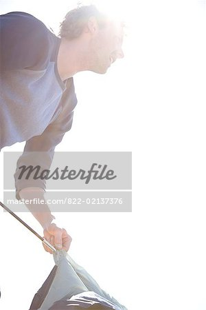 Portrait of young man inserting tent pole into tent Stock Photo - Rights-Managed, Image code: 822-02137376