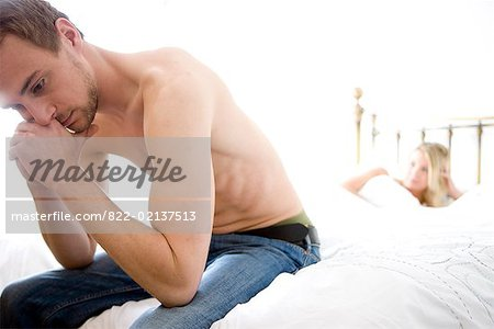 Man sitting at the end of bed with woman lying in bed Stock Photo - Rights-Managed, Image code: 822-02137513