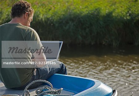 Back view of a man sitting on a boat using a laptop computer Stock Photo - Rights-Managed, Image code: 822-02315685