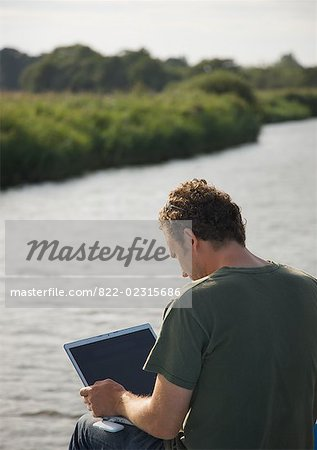 Back view of a man sitting by a river using a laptop computer Stock Photo - Rights-Managed, Image code: 822-02315686