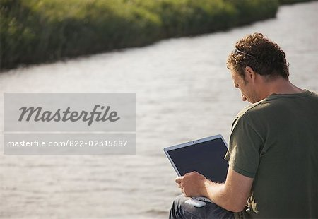 Back view of a man sitting by a river using a laptop computer Stock Photo - Rights-Managed, Image code: 822-02315687