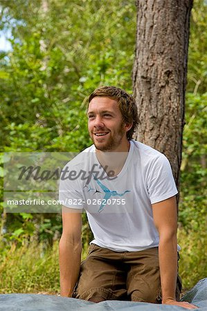 Smiling man kneeling on a groundsheet at campsite Stock Photo - Rights-Managed, Image code: 822-02620755
