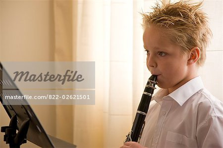 Boy standing in front of a music stand playing the clarinet Stock Photo - Rights-Managed, Image code: 822-02621501