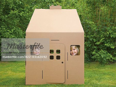Boy and girl looking out from the windows of a cardboard playhouse Stock Photo - Rights-Managed, Image code: 822-03162092