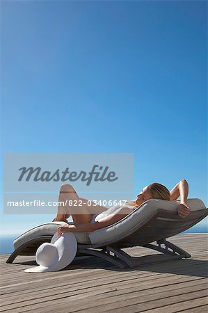 Woman sunbathing on a sun lounger against blue sky Stock Photo - Rights-Managed, Image code: 822-03406647