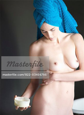 Portrait of a nude woman with towel wrapped over head applying body lotion Stock Photo - Rights-Managed, Image code: 822-03406785