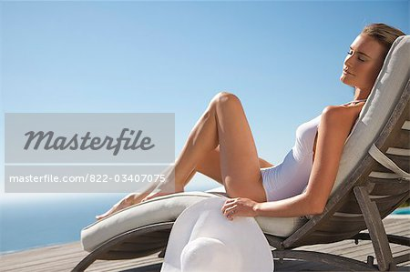 Woman sunbathing on a sun lounger against blue sky Stock Photo - Rights-Managed, Image code: 822-03407075